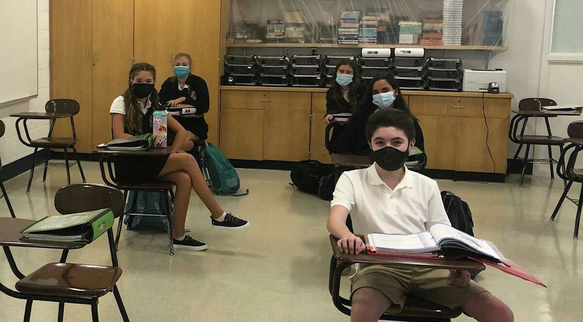 Eighth-graders at Greenwich Catholic School settle in at their socially-distanced desks on the first day of classes on Wednesday.