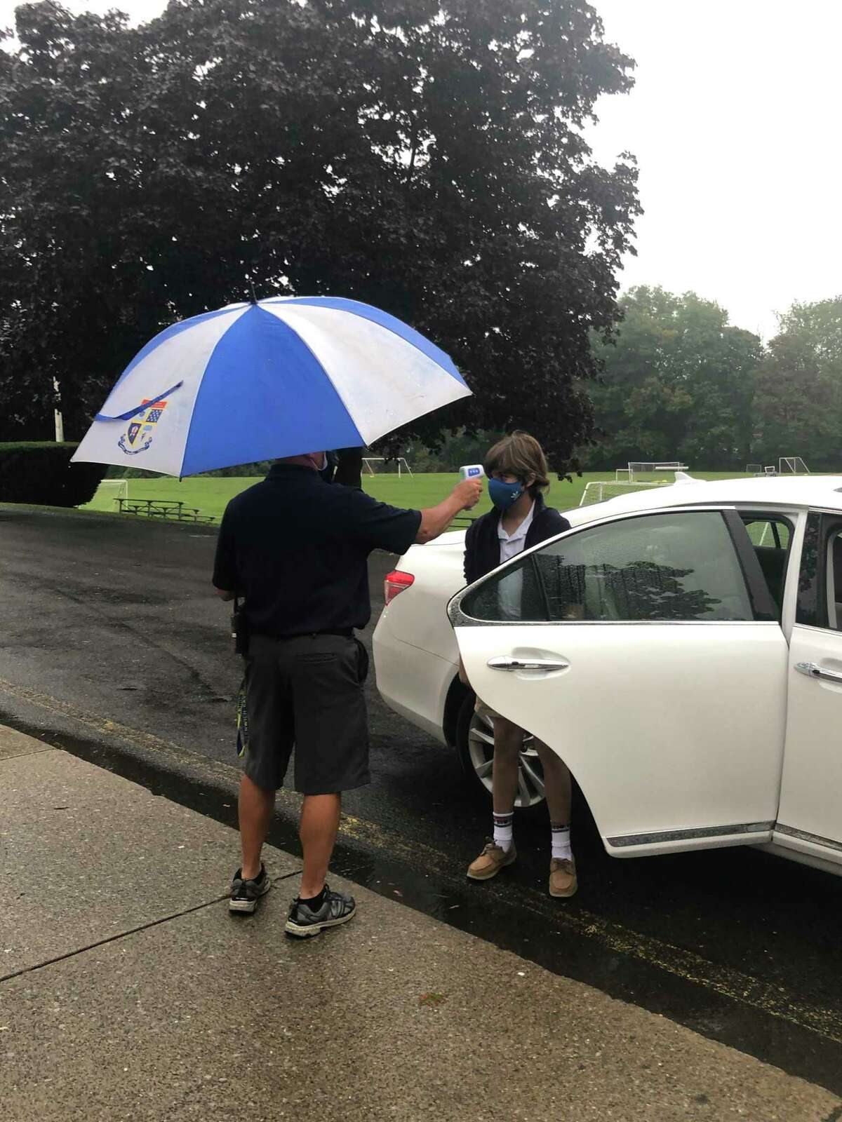 A staff members checks the temperature of a seventh-grader as the student arrives for the first day of school at Greenwich Catholic School.