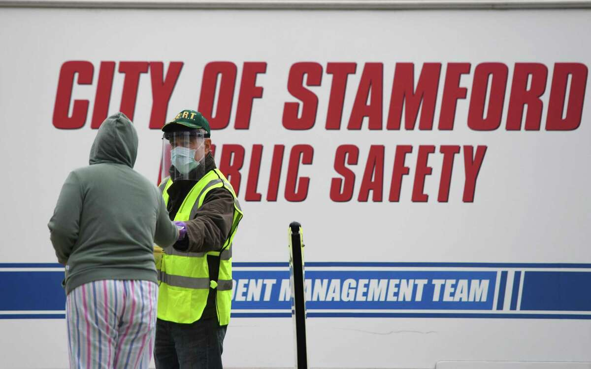 Stamford's Community Emergency Response Team distributes masks at a drive-thru at Stamford High School in Stamford, Conn. Sunday, April 26, 2020.