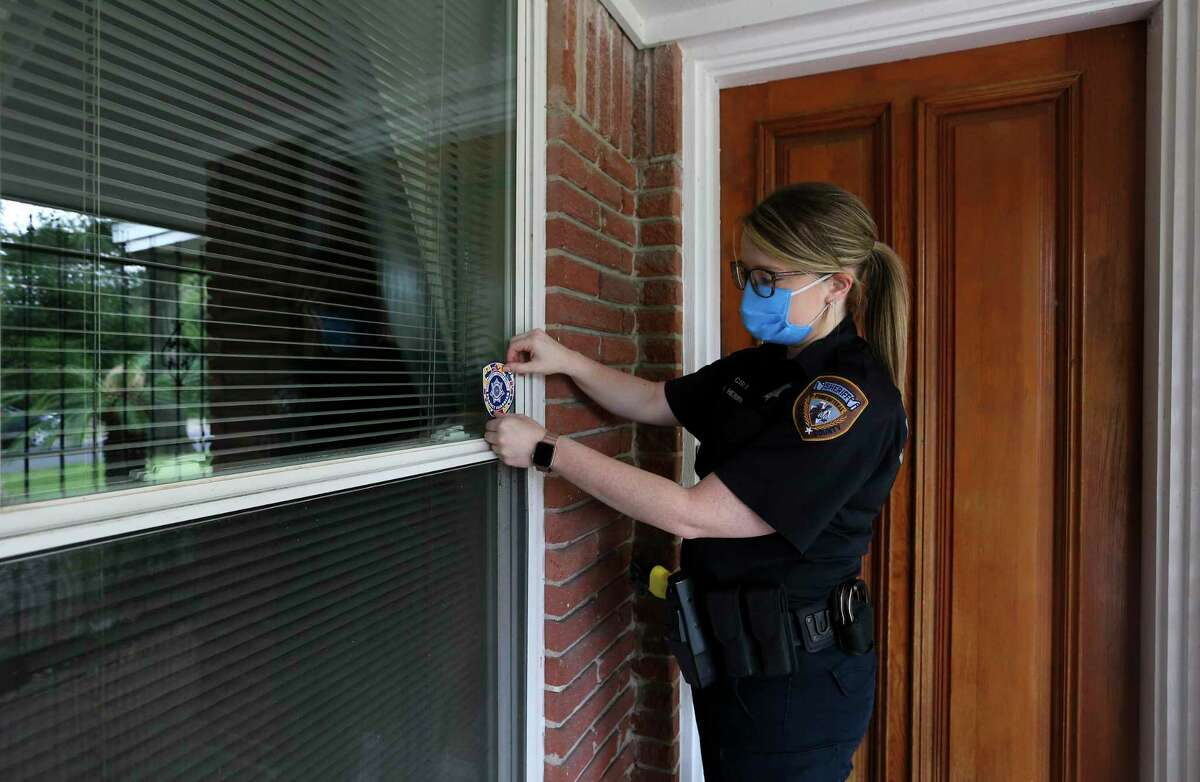 Harris County sheriff's Deputy Megan Herrin affixes a Project Guardian sticker on a front window of a home in west Houston. Project Guardian is a new initiative from the Harris County Sheriff's Office that lets families register a loved one with autism so that if deputies are ever called to their home, they arrive prepared to interact with the individual in a way that won't antagonize or cause undue stress.