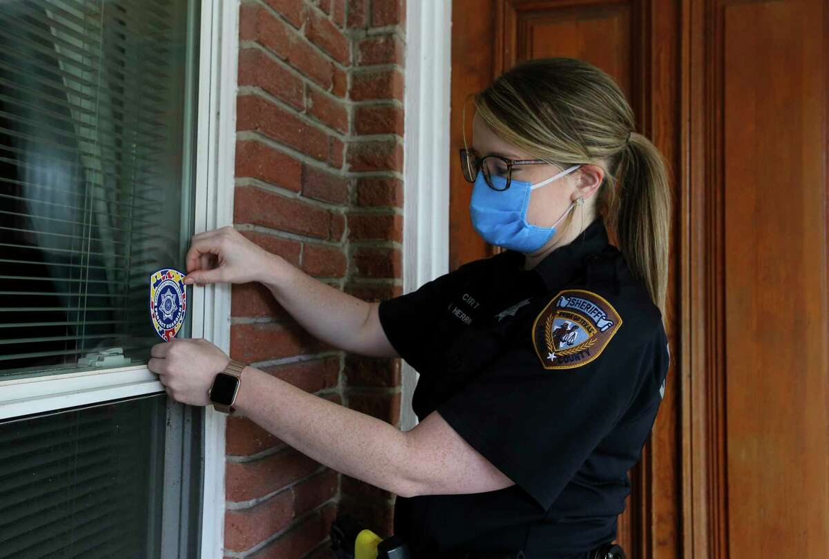 Harris County sheriff's Deputy Megan Herrin affixes a Project Guardian sticker to a front window of a home in west Houston. The voluntary registry lets families provide information about their loved one with autism, which is relayed to deputies responding to a call at the person's residence.