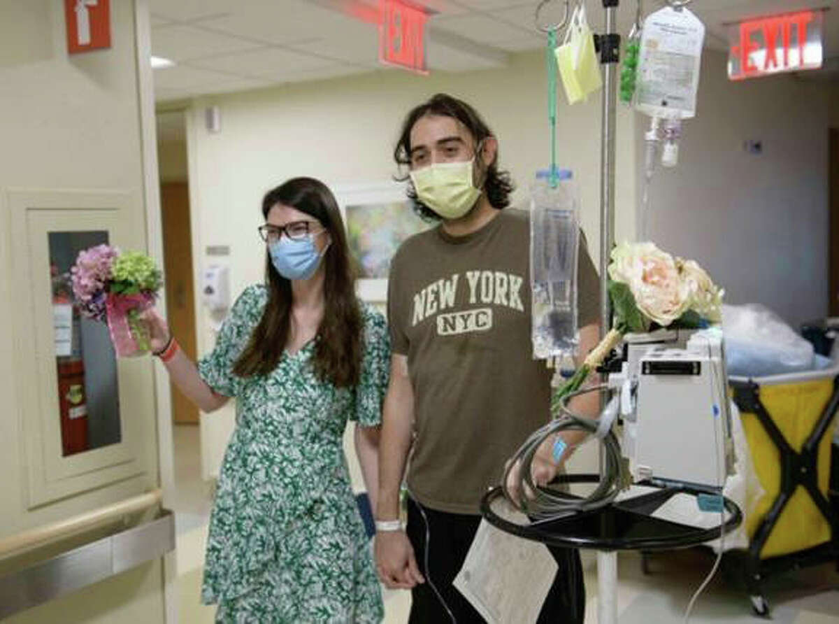 Miranda Wickham, left, and Enver Candan head to a conference room at Memorial Sloan Kettering Cancer Center in New York to get married on Aug. 7. Candan was being treated at the hospital for acute leukemia.