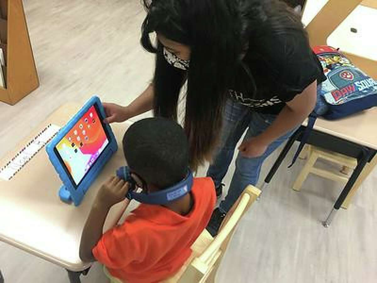 A teacher helps a student at the Spring Branch ISD Employee Childcare Center