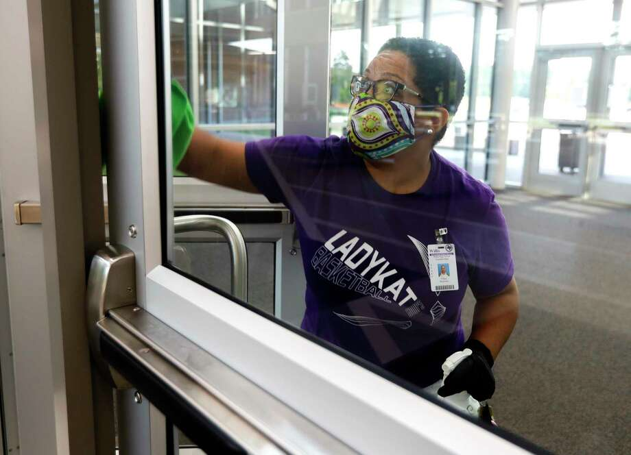 Custodian Tiffany Blackman sanitizes high-touch surfaces at the enterance to Willis ISD's Career and Technology Education Center, Thursday, Aug. 6, 2020, in Willis. Photo: Jason Fochtman, Houston Chronicle / Staff Photographer / 2020 © Houston Chronicle