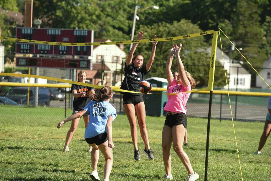 The Stamford girls volleyball team practices outdoors on the school's varsity softball field during the first week of conditioning and practices for 2020. Three nets were set up on the field and keeping with COVID protocols, players were grouped in small cohorts of fewer than 10, and maintained social distancing with six feet between players. Photo: Dave Stewart / Hearst Connecticut Media / Hearst Connecticut Media