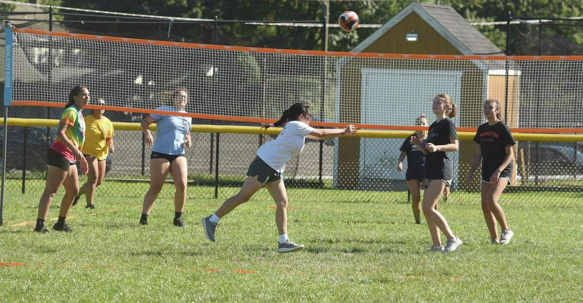 The Stamford girls volleyball team practices outdoors on the school's varsity softball field during the first week of conditioning and practices for 2020. Three nets were set up on the field and keeping with COVID protocols, players were grouped in small cohorts of fewer than 10, and maintained social distancing with six feet between players.