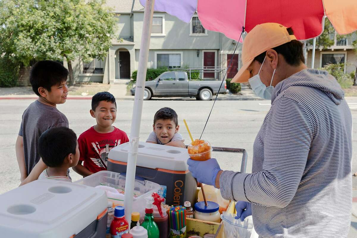 (Left to right) Jeremias, Jonathan, Chris and Darbi (no last names given) buy a �Mangonada� from vendor Jose Gonzales in the Canal neighborhood of San Rafael, Calif., on Wednesday, August 19, 2020.