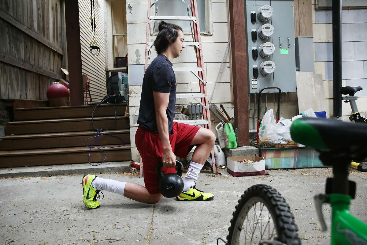Alexander Massialas works out with a weight in the backyard of his San Francisco home.Fencing is one of the 11 sports Stanford is eliminating.