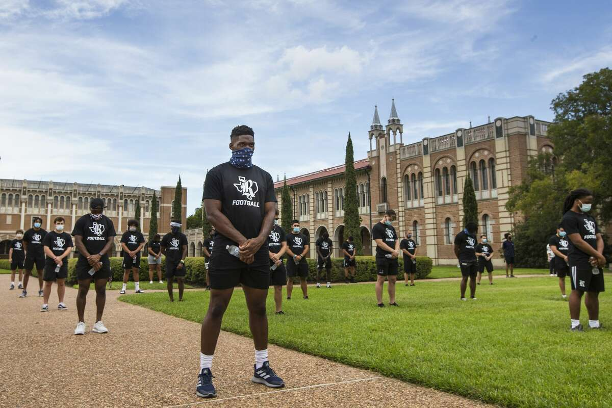 Rice University football player Ikenna Enechukwu, center, left, stands with a group of his teammates following a march across campus in a show of unity by the team to protest systemic racism on Friday, Sept. 4, 2020 in Houston. The players started in Rice Stadium and marched across the campus for a socially distanced rally in the Academic Quad on campus.