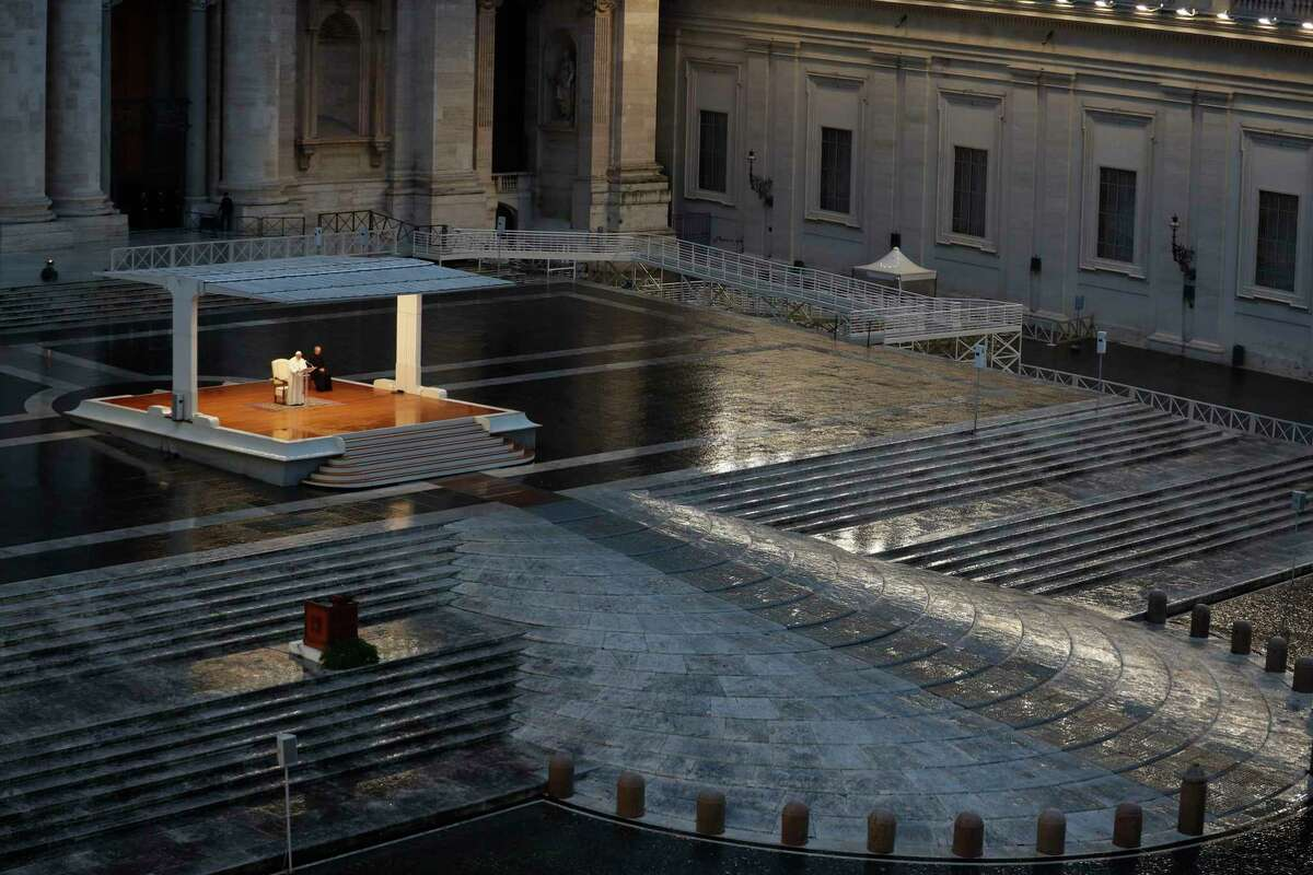 FILE - In this photo taken on March 27, 2020, Pope Francis, white figure standing alone at center, delivers an Urbi et orbi prayer from the empty St. Peter's Square, at the Vatican. If ever there was a defining moment of Pope Francis during the coronavirus pandemic, it came on March 27, the day Italy recorded its single biggest daily jump in fatalities. From the rain-slicked promenade of St. Petera€™s Basilica, Francis said the virus had shown that wea€™re all in this together, that we need each other and need to reassess our priorities. (Yara Nardi/Pool Photo via AP )