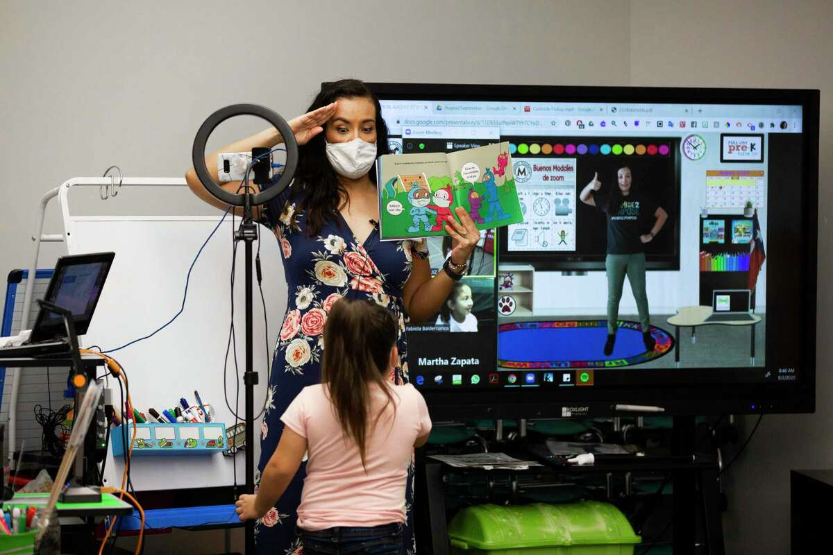 Mahaffey Elementary School kindergarten teacher Teresita Ruiz shows one of her students alternative ways to greet instead of hugs or hand shaking during a simulation class on Wednesday, Sept. 2, 2020, in Tomball ahead of the first day of school on September 8, 2020.
