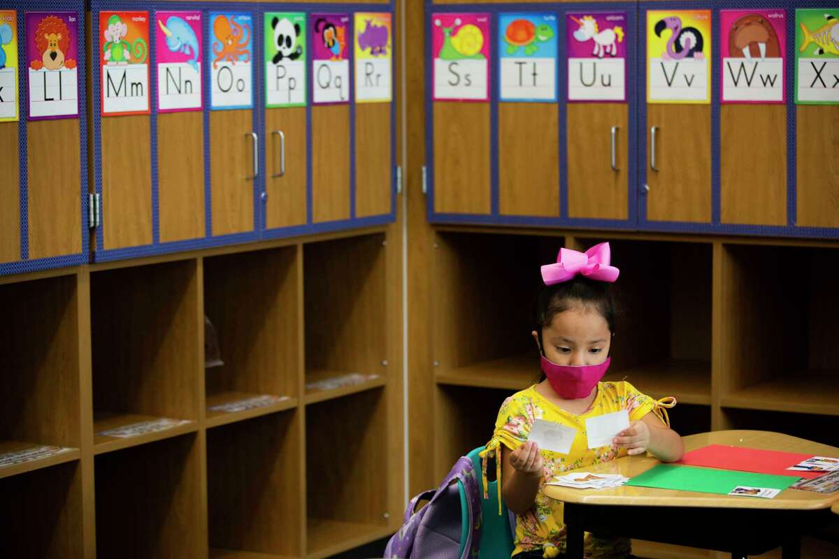 A Mahaffey Elementary School kindergarten student wearing a protective mask, looks at images that show proper examples of conduct during a simulation class on Wednesday, Sept. 2, 2020, in Tomball, ahead of the first day of school on September 8, 2020.