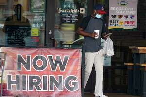 A customer wears a mask and looks at their cell phone as they carry their order past a now hiring sign at an eatery in Richardson, Texas, Wednesday, Sept. 2, 2020. The U.S. unemployment rate fell sharply in August to 8.4% A from 10.2% even as hiring slowed in August as employers added the fewest jobs since the pandemic began. (AP Photo/LM Otero)