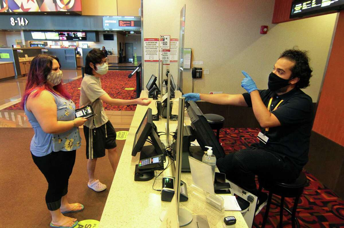 Dui Crell of Hamden gets tickets from employee Raymond Gomez at Cinemark Theater in North Haven Sept. 3, 2020. At left is Dui's friend Olivia Ransohoff of Hamden.