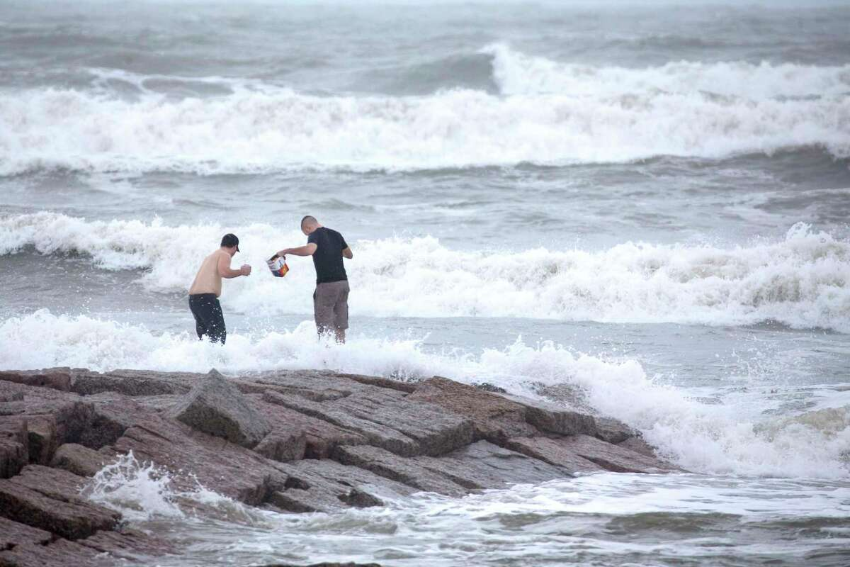 Alex Mazzucco, left, and Nathan Wilson stand out on a jetty watching the surf stirred up by Hurricane Laura Wednesday, Aug. 26, 2020 in Galveston.