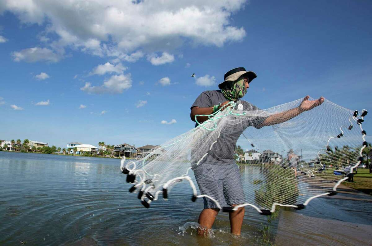 Roberto Del Angel casts a net while fishing with family Thursday, Aug. 27, 2020, in Seabrook. Hurricane Laura made landfall near Cameron, Louisiana, early Thursday morning and did not impact the Houston area.