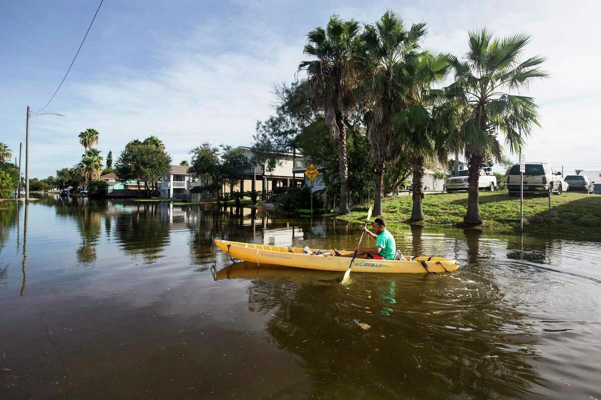Martin Almanza paddles a canoe through some street flooding following landfall of Hurricane Laura on Thursday, Aug. 27, 2020 in Galveston. The island city was spared after came ashore east of the Texas/Louisiana border overnight.