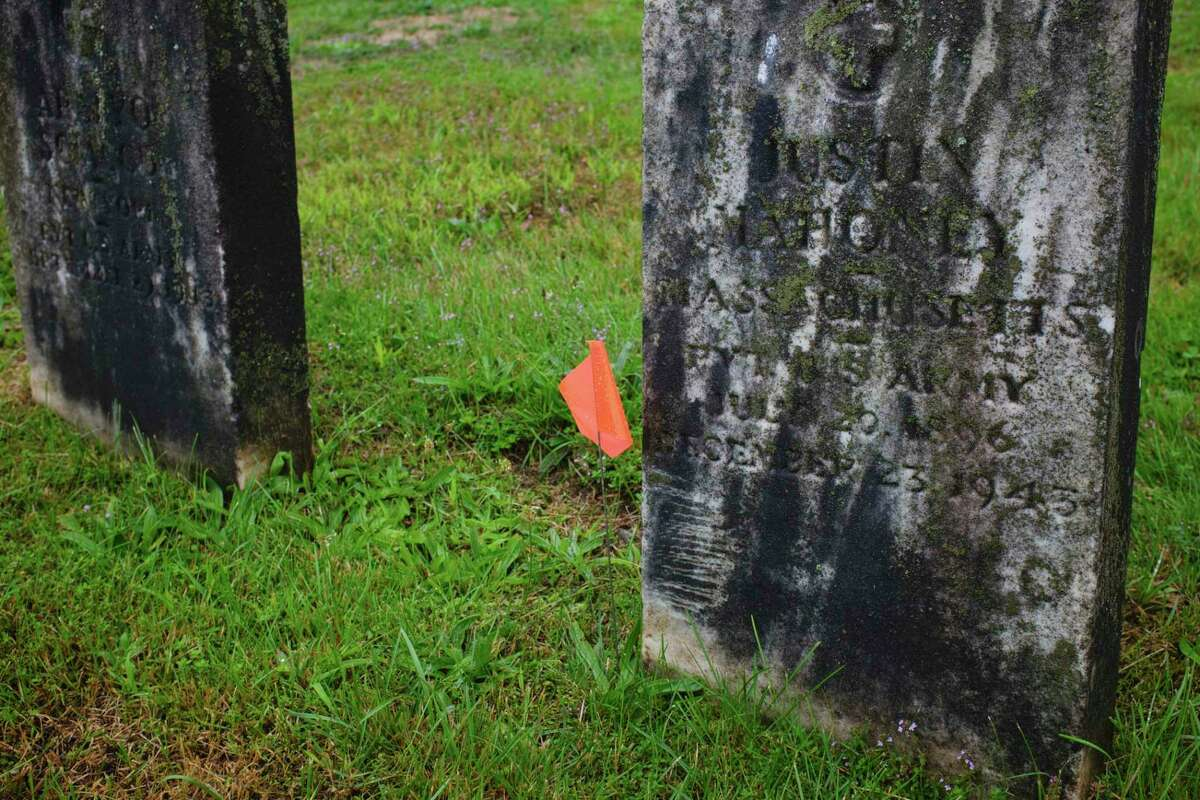 A orange flag signifies that someone has donated money to have the headstone of a veteran cleaned at St. Mary's Cemetery on Wednesday, Sept. 2, 2020, in Troy, N.Y. Albany Diocesan Cemeteries Historian Kelly Grimaldi is heading up the project to get the headstones cleaned up. (Paul Buckowski/Times Union)