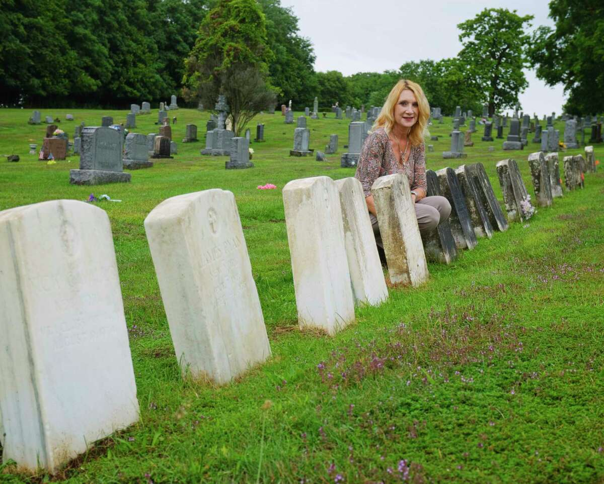 Albany Diocesan Cemeteries Historian Kelly Grimaldi poses next to a cleaned up headstone of a World War I veteran at St. Mary's Cemetery on Wednesday, Sept. 2, 2020, in Troy, N.Y. Grimaldi is heading up the project to get the headstones cleaned up. (Paul Buckowski/Times Union)