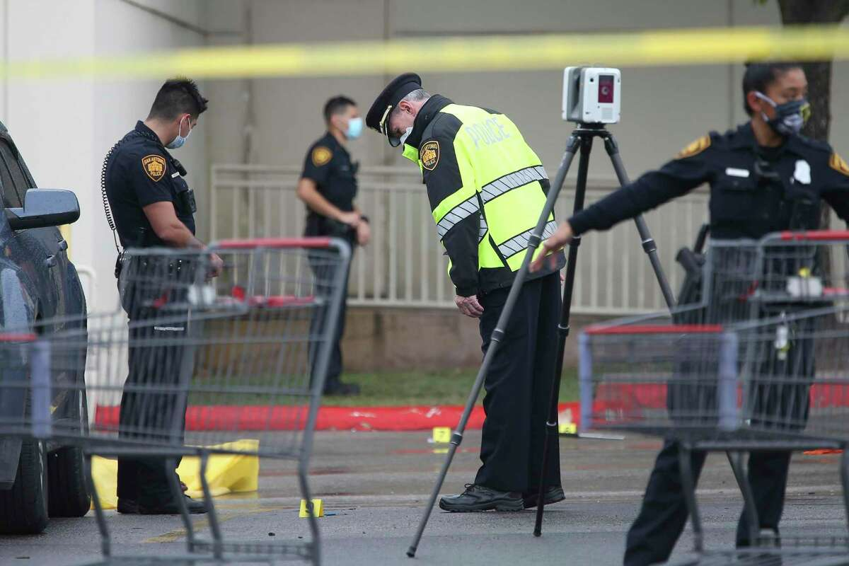 Police Chief William McManus looks at evidence at the scene of the fatal confrontation. Officials did not say what the shoplifting suspect was accused of attempting to steal from the H-E-B store.