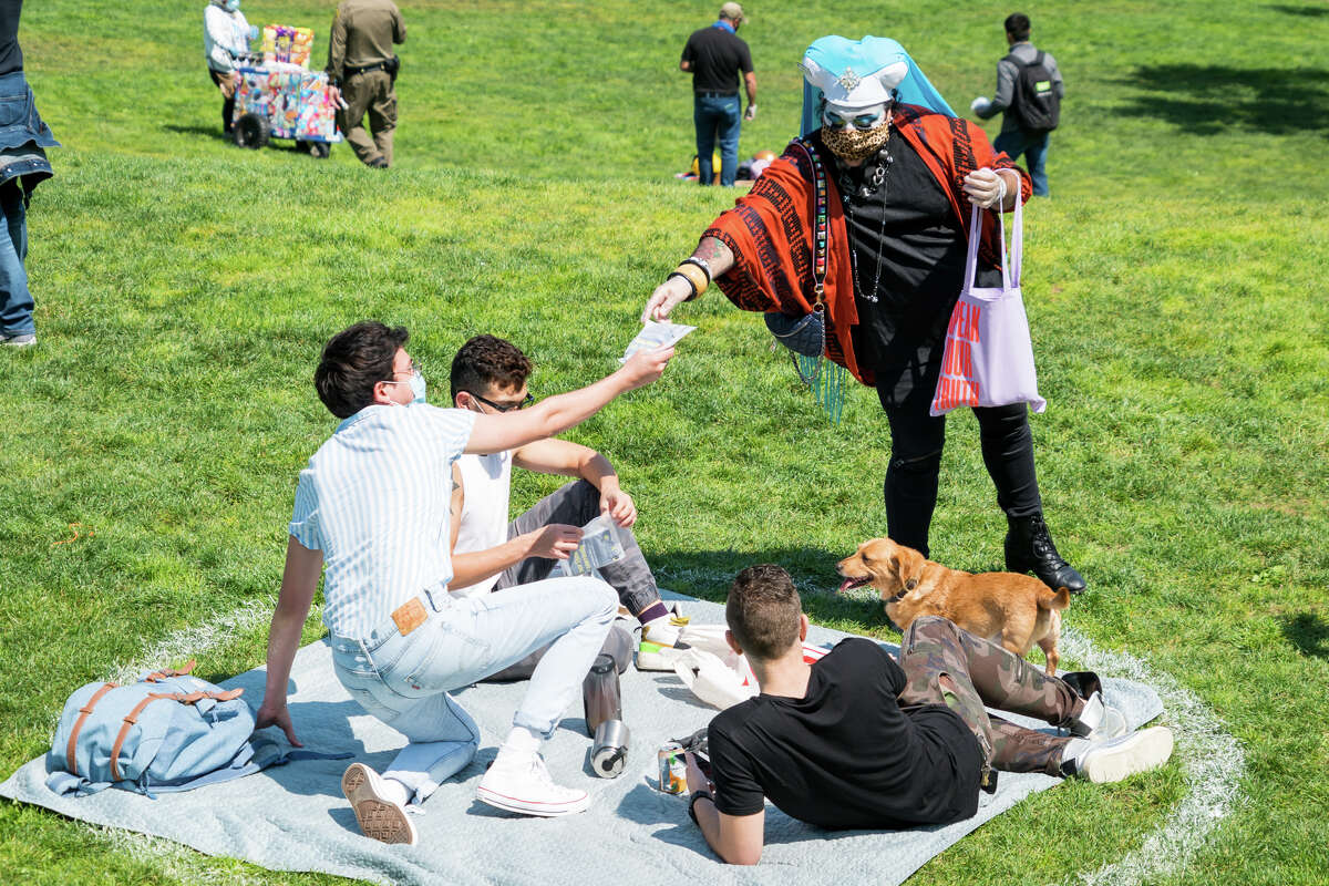 One of the Sisters of Perpetual Indulgence hands out face masks in Dolores Park on Sept. 4, 2020.