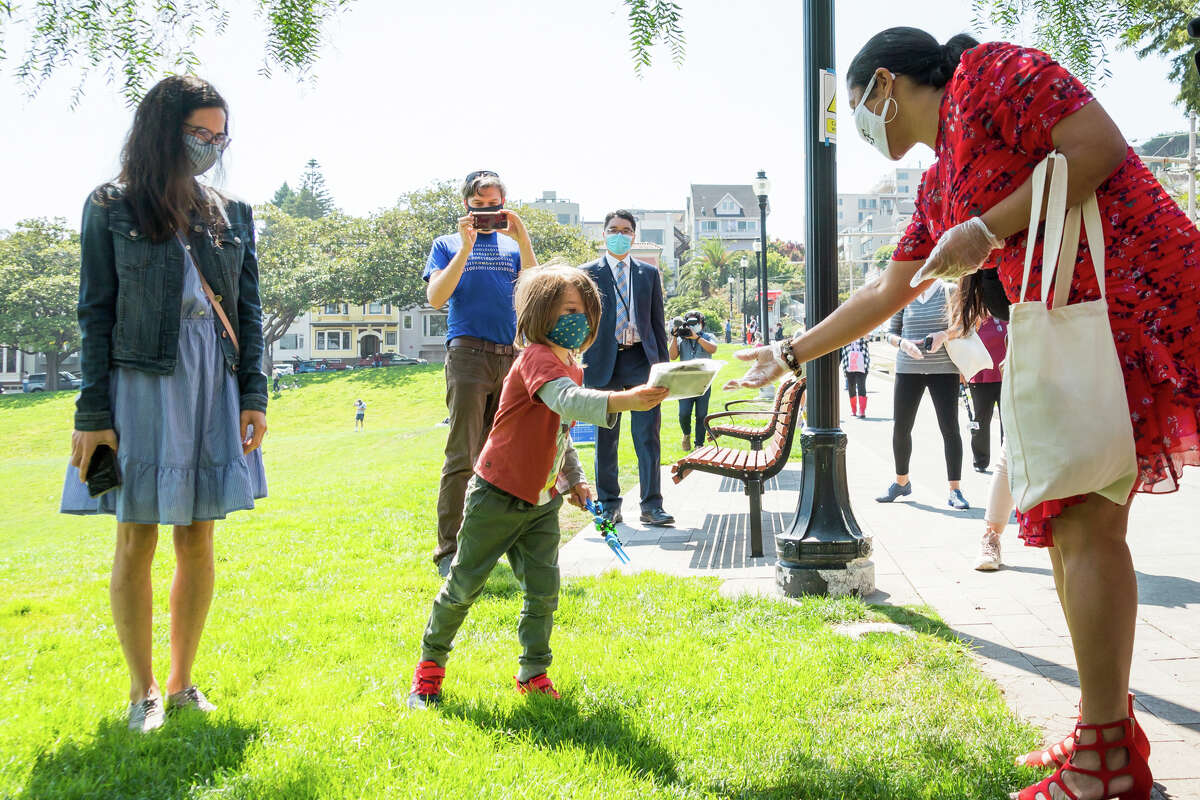 San Francisco Mayor London Breed hands out a mask to a young child at Dolores Park on Sept. 4, 2020. S