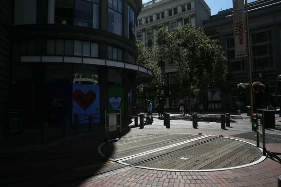 Pedestrians walk past an empty cable car turntable at the Powell and Market Street cable car turnaround on Wednesday, July 8, 2020 in San Francisco, Calif.