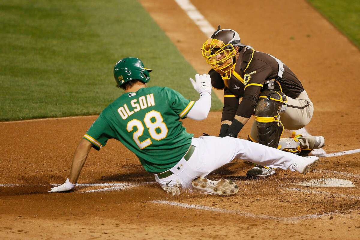 Oakland Athletics first baseman Matt Olson (28) slides to home plate against San Diego Padres catcher Austin Nola (22) in the fourth inning of an MLB game at RingCentral Coliseum on Friday, Sept. 4, 2020, in Oakland, Calif. Initially called safe, Olson was ruled out after official review of the play.