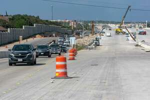 Southbound traffic, left, enters an expanded section of U.S. 281 on Thursday south of Evans Road as work continues, right, on still-under-construction sections of the highway expansion.
