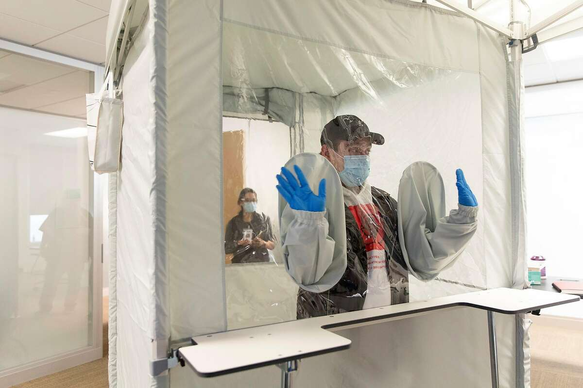 Rafael Gonzalez, a community program manager with Bridge HIV, checks out the new tent that will allow him and his co-workers to safely get nasal swabs from COVID19 vaccine trial participants at Bridge HIV in San Francisco, Calif., Thursday, Sept. 3, 2020.