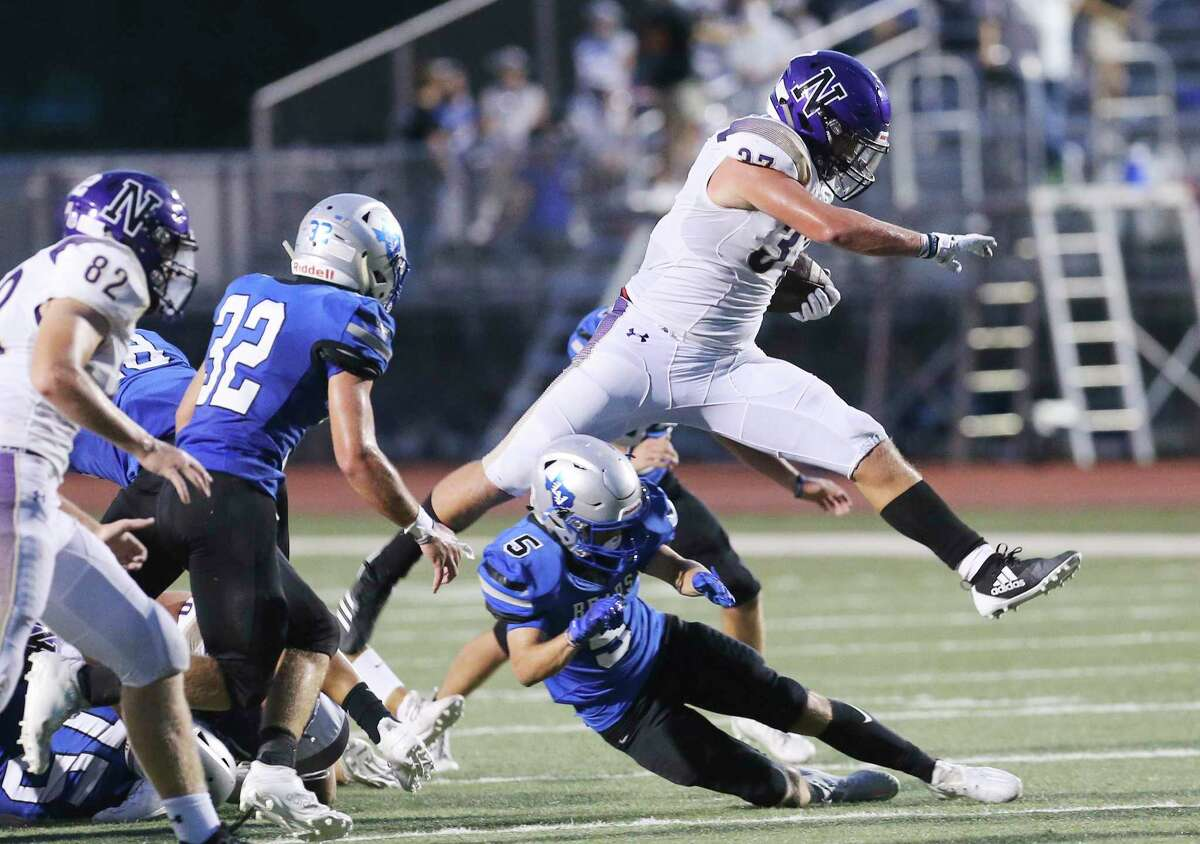 Navarro's Brody Whitson (37) leaps over La Vernia's Zach Simon (05) during their football game at La Vernia on Friday, Sept. 4, 2020.