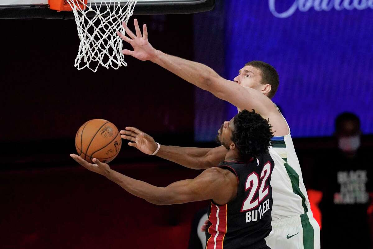 Miami Heat's Jimmy Butler (22) shoots as Milwaukee Bucks' Brook Lopez (11) defends in the second half of an NBA conference semifinal playoff basketball game Friday, Sept. 4, 2020, in Lake Buena Vista, Fla. (AP Photo/Mark J. Terrill)