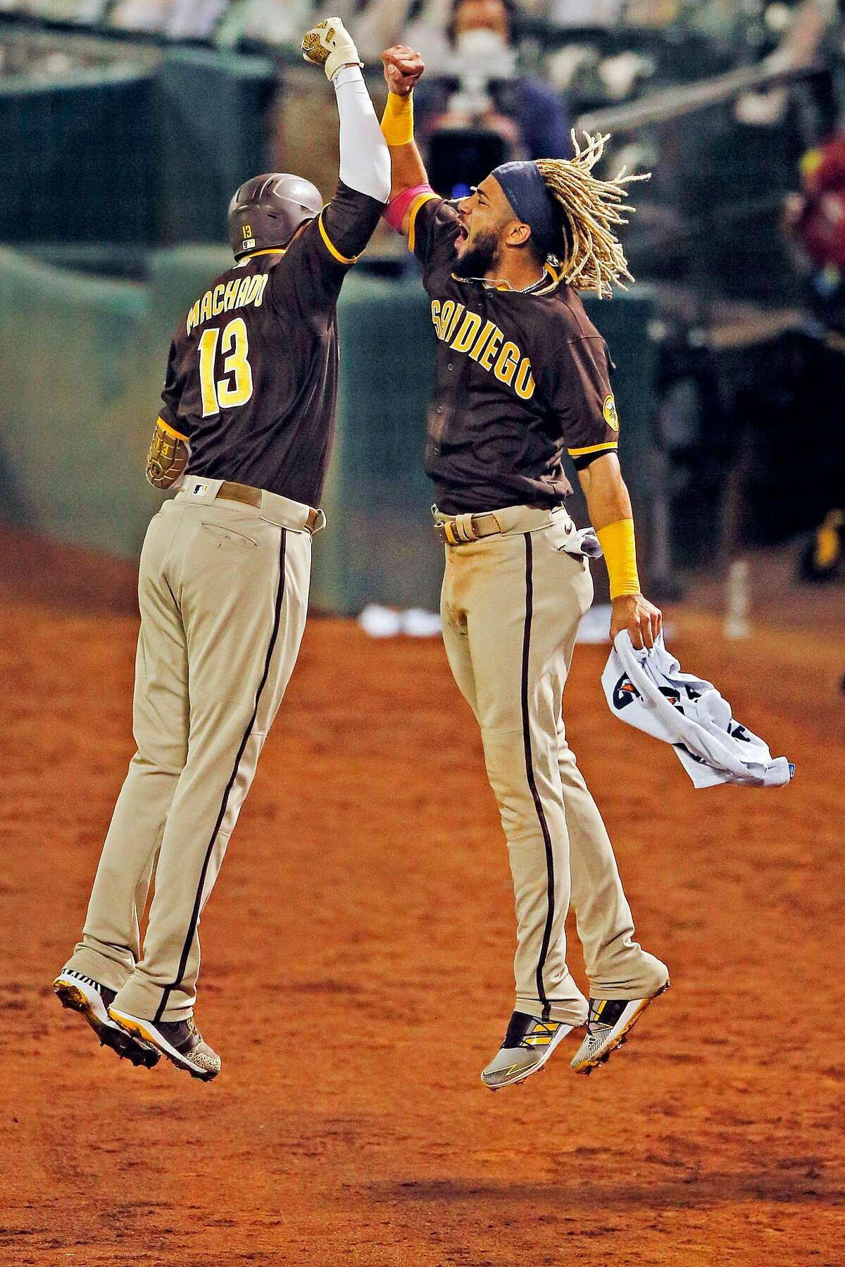 From left: San Diego Padres third baseman Manny Machado (13) and Padres shortstop Fernando Tatis Jr. (23) celebrate Machado's home run in the seventh inning of an MLB game against the Oakland Athletics at RingCentral Coliseum on Friday, Sept. 4, 2020, in Oakland, Calif.