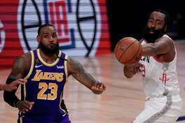 Houston Rockets' James Harden (13) passes in front of Los Angeles Lakers' LeBron James (23) during the second half of an NBA conference semifinal playoff basketball game Friday, Sept. 4, 2020, in Lake Buena Vista, Fla. (AP Photo/Mark J. Terrill)