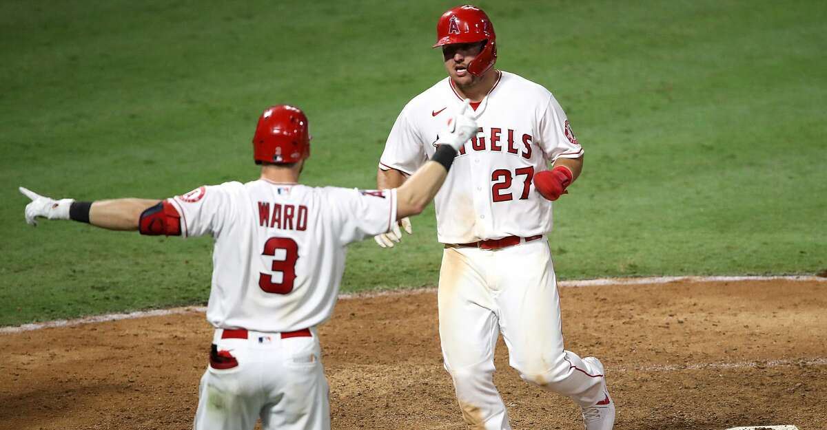 ANAHEIM, CALIFORNIA - SEPTEMBER 04: Taylor Ward #3 congratulates Mike Trout #27 after he scored on an RBI single hit by Shohei Ohtani #17 of the Los Angeles Angels during the eleventh inning to defeat the Houston Astros 6-5 in a game at Angel Stadium of Anaheim on September 04, 2020 in Anaheim, California. (Photo by Sean M. Haffey/Getty Images)