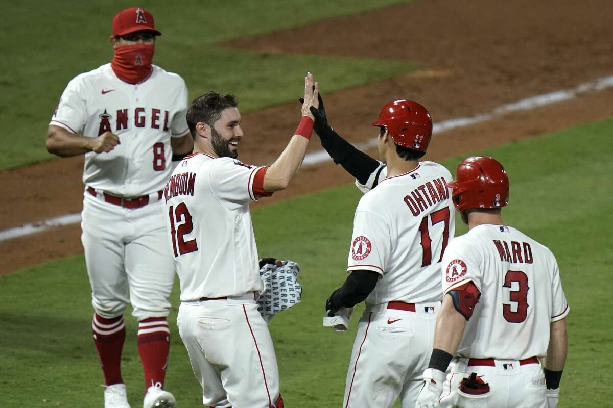 Los Angeles Angels' Shohei Ohtani, second from right, is congratulated by Anthony Bemboom after driving in the winning run in the 11th inning of the team's baseball game against the Houston Astros, Friday, Sept. 4, 2020, in Anaheim, Calif. The Angels won 6-5. (AP Photo/Jae C. Hong)
