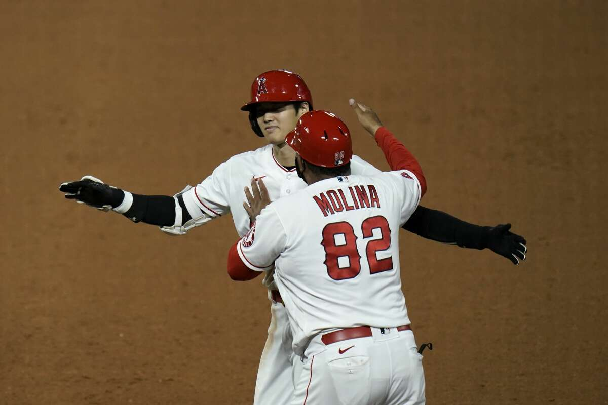 Los Angeles Angels' Shohei Ohtani, of Japan, celebrates with first base coach Jose Molina after driving in the winning run with a single during the 11th inning of the team's baseball game against the Houston Astros, Friday, Sept. 4, 2020, in Anaheim, Calif. The Angels won 6-5. (AP Photo/Jae C. Hong)