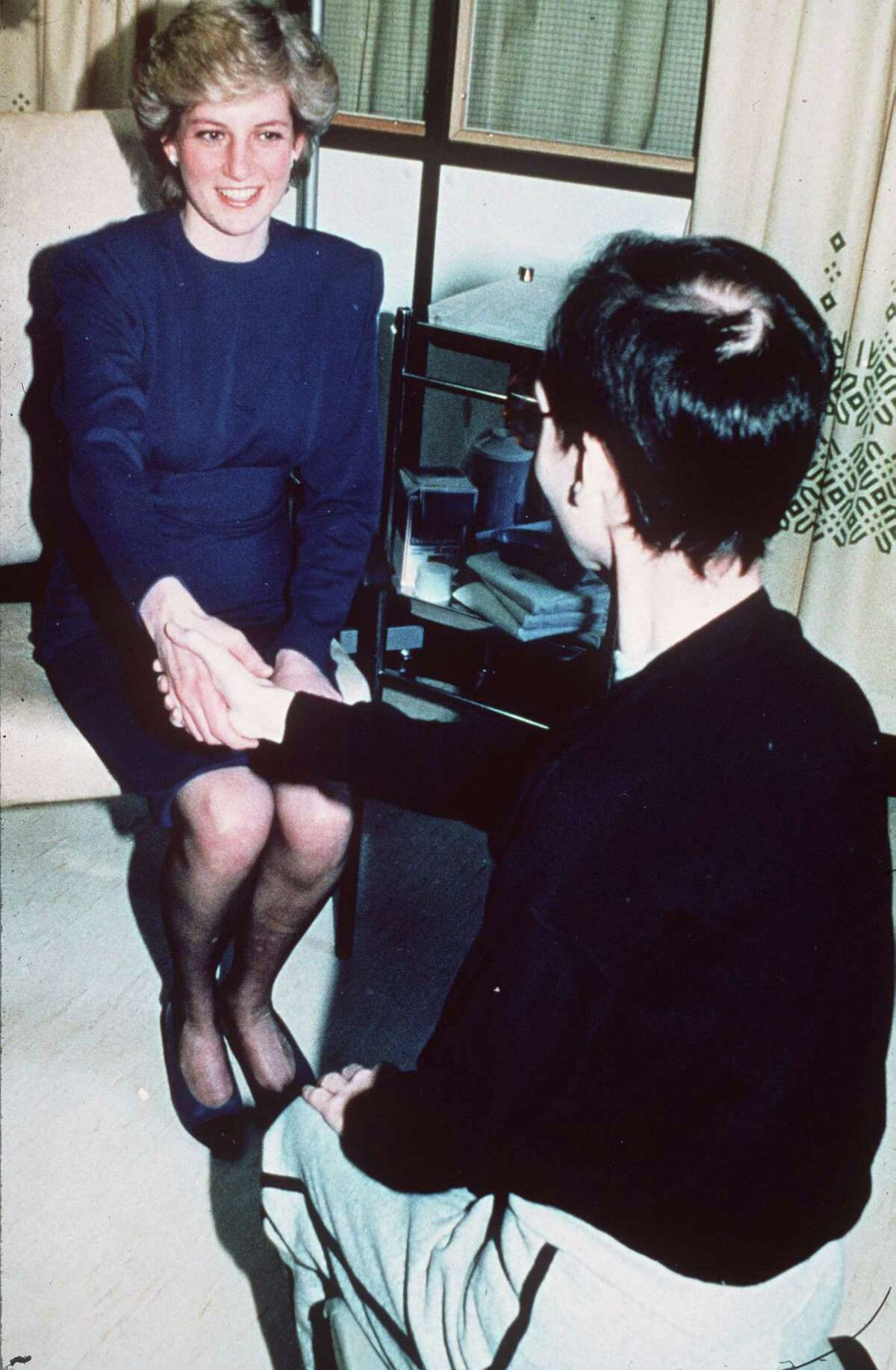 Princess Diana is also long remembered by some queer people for her unapologetic advocacy for AIDS patients and awareness about HIV, the virus that causes AIDS, as pictured above as she shakes the hand of an AIDS patient during her visit to the opening of the United Kingdom's first hospital AIDS unit in 1987.