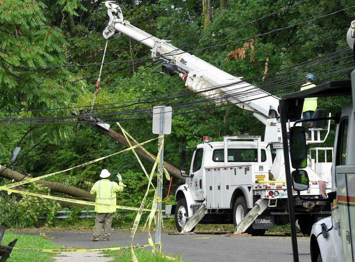 A utility crew works to erect a downed pole on Taylor Street on August 7, 2020 in Stamford, Connecticut. Many out of state crews have been brought in to assist Eversource in restoring power to the region and help with clean up of storm debris left in the wake of Tropical Storm Isaias