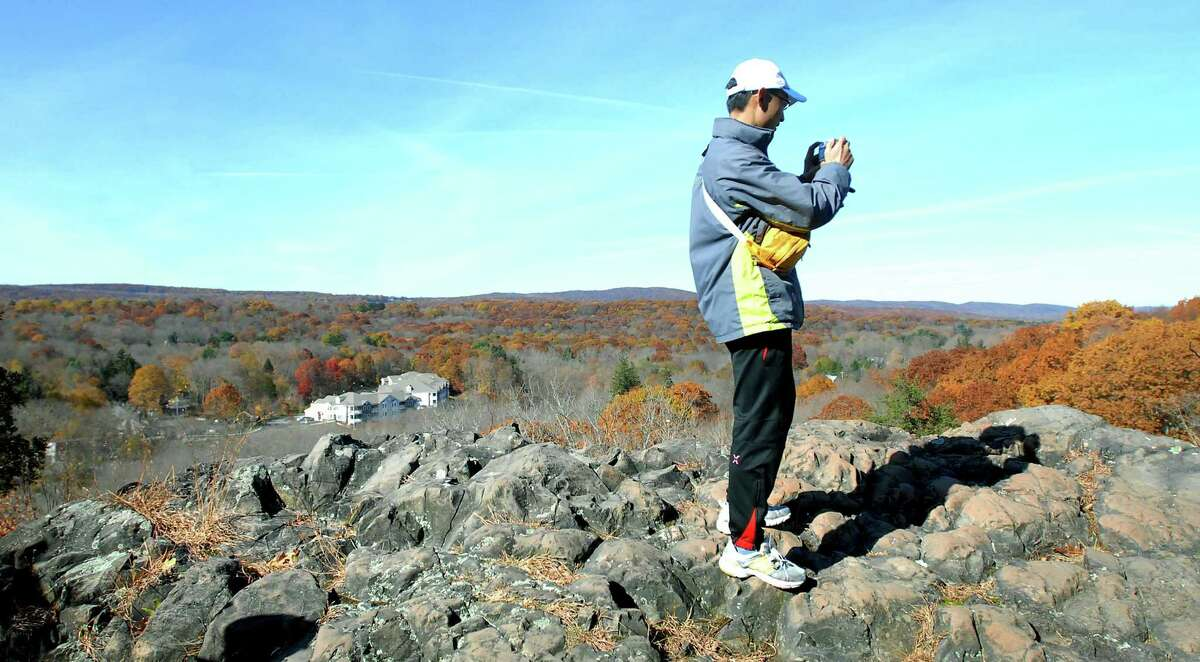 A hiker takes a photograph on a rock summit at Sleeping Giant State Park in Hamden during the Fall Hikers' Hike hosted by the Sleeping Giant Park Association in November 2008.