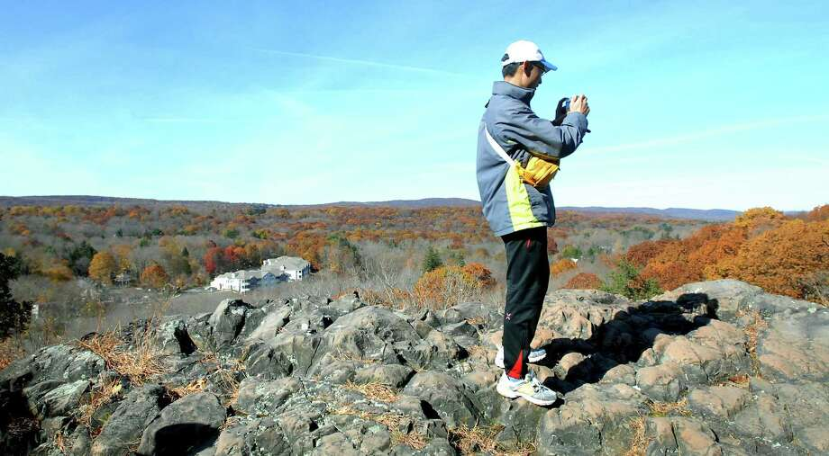 A hiker takes a photograph on a rock summit at Sleeping Giant State Park in Hamden during the Fall Hikers' Hike hosted by the Sleeping Giant Park Association in November 2008. Photo: Hearst Connecticut Media File Photo