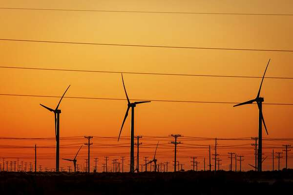 Power lines are dwarfed by several 285ft tall 2.5 MW Clipper wind turbines at the BP Sherbino Mesa II Wind Farm, Monday, Feb. 20, 2012, in Fort Stockton. After cutting its solar program last year, BP is beefing up its investments into wind energy and recently launched its fourth Texas wind farm, in Fort Stockton. On 20,000 acres in Pecos County, the Sherbino II farm has 60 wind turbines to generate enough electricity to power more than 175,000 homes. ( Michael Paulsen / Houston Chronicle )
