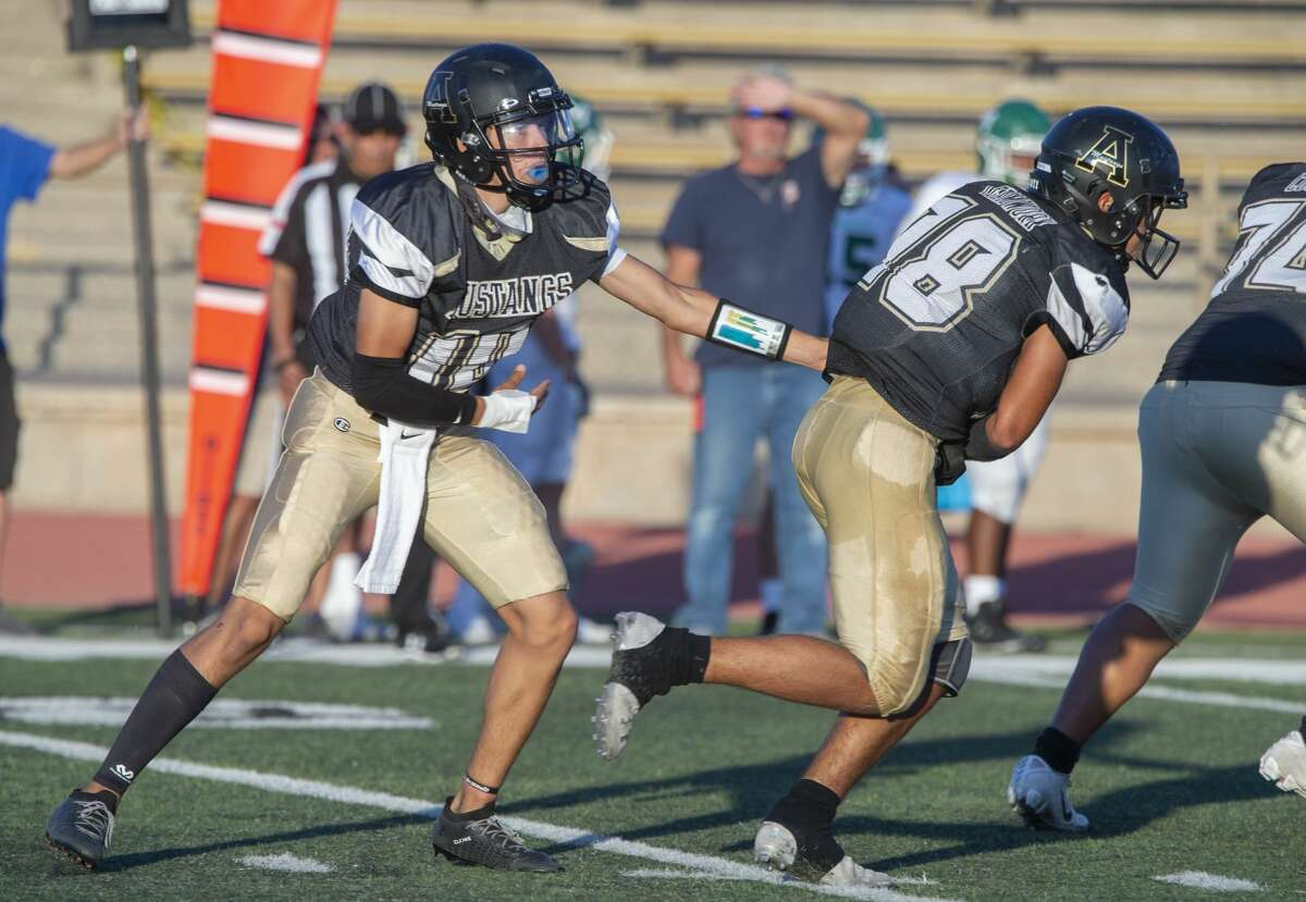 Andrews' quarterback E.J. Lopez hands off to Luis Cervantes 09/04/2020 at the Andrews Mustang Bowl as they battle Monahans. Tim Fischer/Reporter-Telegram