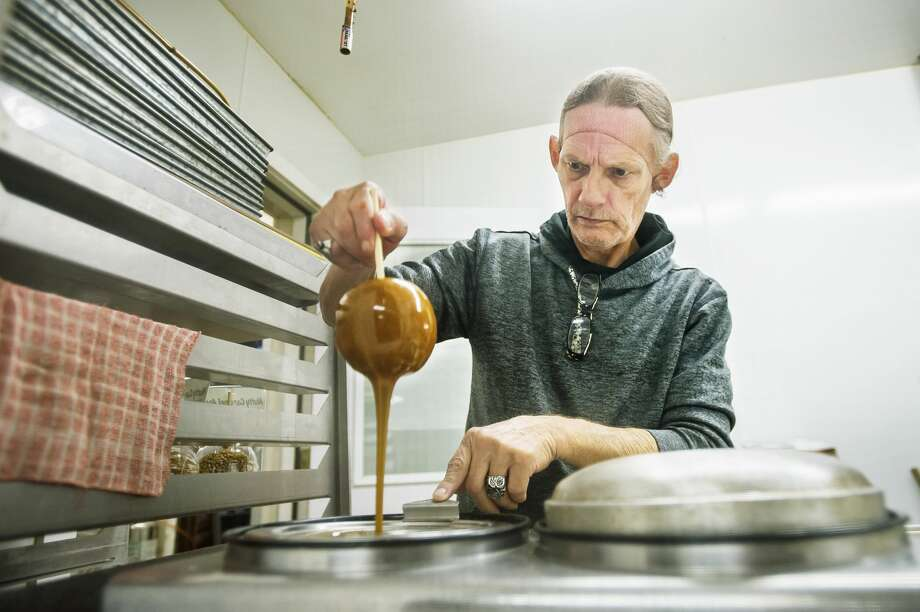 Glen Johnson dips a Ginger Gold apple into caramel while making a tray of caramel apples Saturday, Sept. 5, 2020 at Leaman's Green Applebarn in Freeland. (Katy Kildee/kkildee@mdn.net) Photo: (Katy Kildee/kkildee@mdn.net)