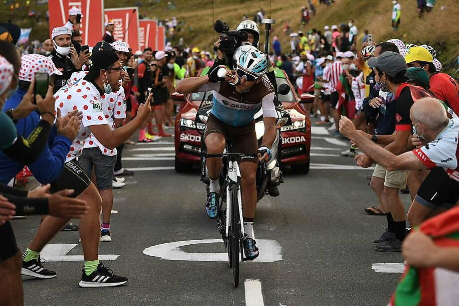 France's Nans Peters rides ahead in the Pyrenees amid non-socially distanced fans with masks askew during Stage 8 the 107th Tour de France. The marquee cycling race has two weeks to go. Photo: Anne-Christine Poujoulat / AFP Via Getty Images