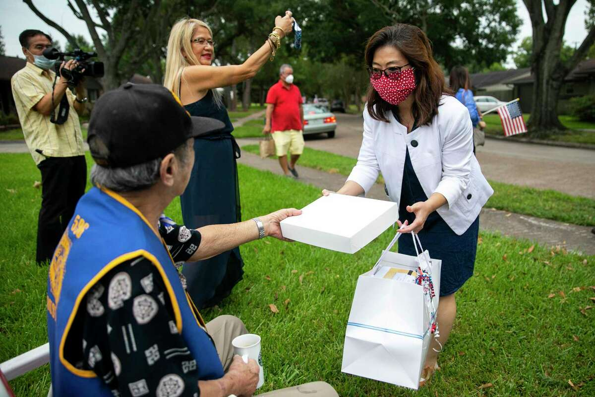 """WWII veteran Henry """"Hank"""" Lee receives a flag from Alice Lee during a parade honoring seven Chinese Americans for the 75th anniversary of the end of WWII hosted by the Chinese American Citizens Alliance in Houston on Saturday, Sept. 5, 2020."""