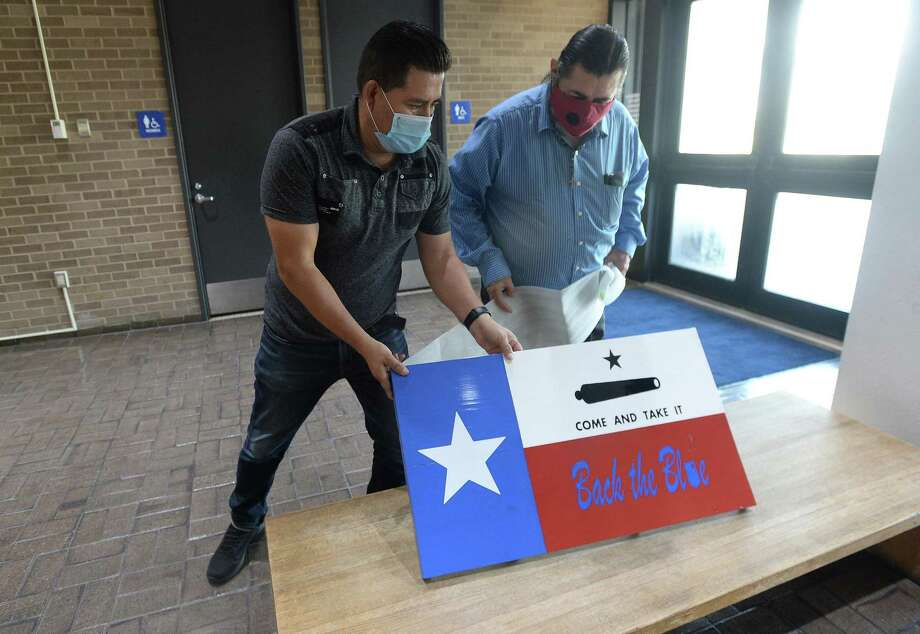 Fernando Ramirez talks with fellow Hispanic media member Joselo Hernandez as they unwrap a handpainted flag plque to present to Beaumont's police union at Beaumont Police headquarters Friday morning.  Photo taken Friday, September 4, 2020 Kim Brent/The Enterprise Photo: Kim Brent / The Enterprise / BEN