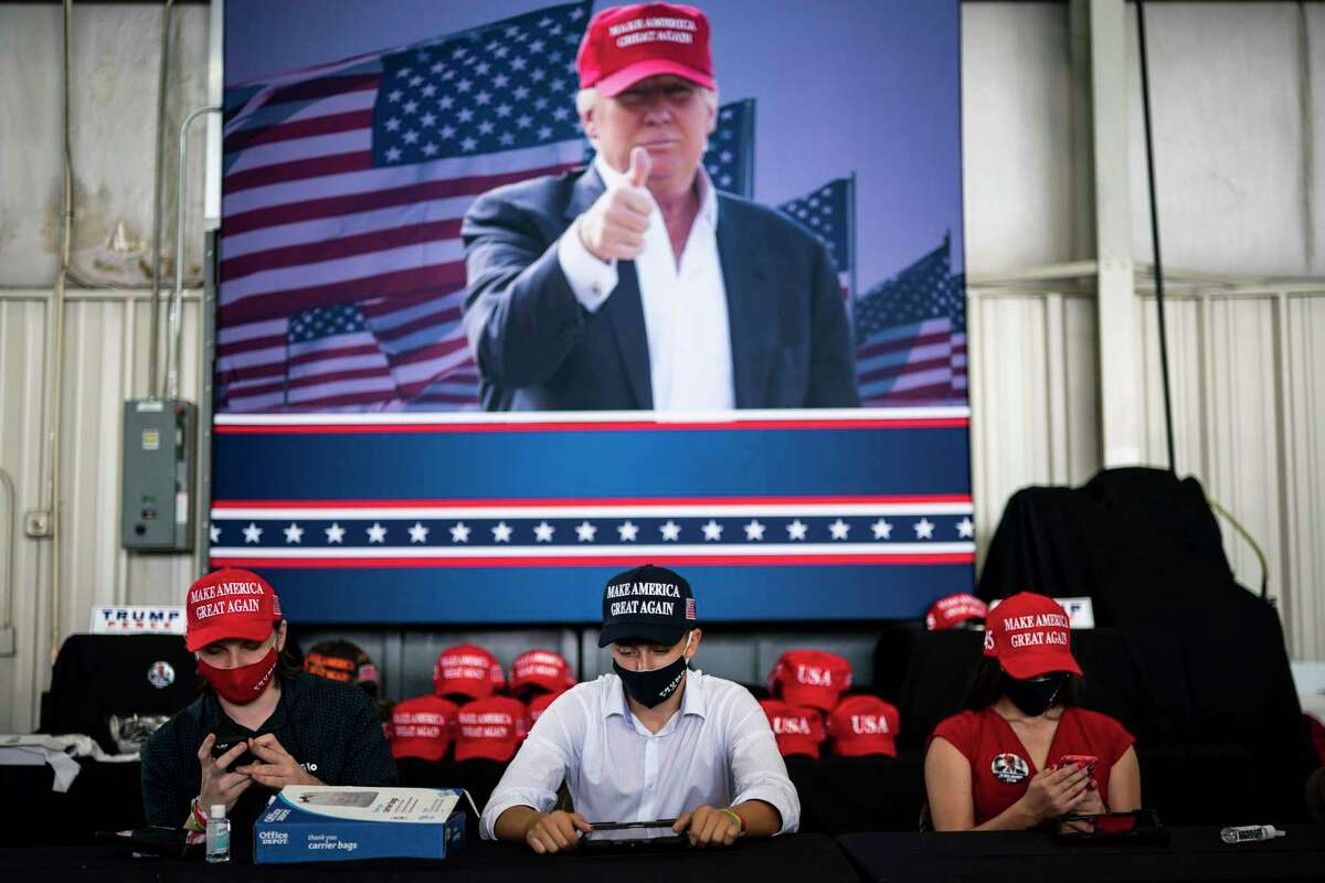 Campaign volunteers wear face masks as they wait for customers at President Trump's rally at Arnold Palmer Regional Airport in Latrobe, Pa., on Thursday.