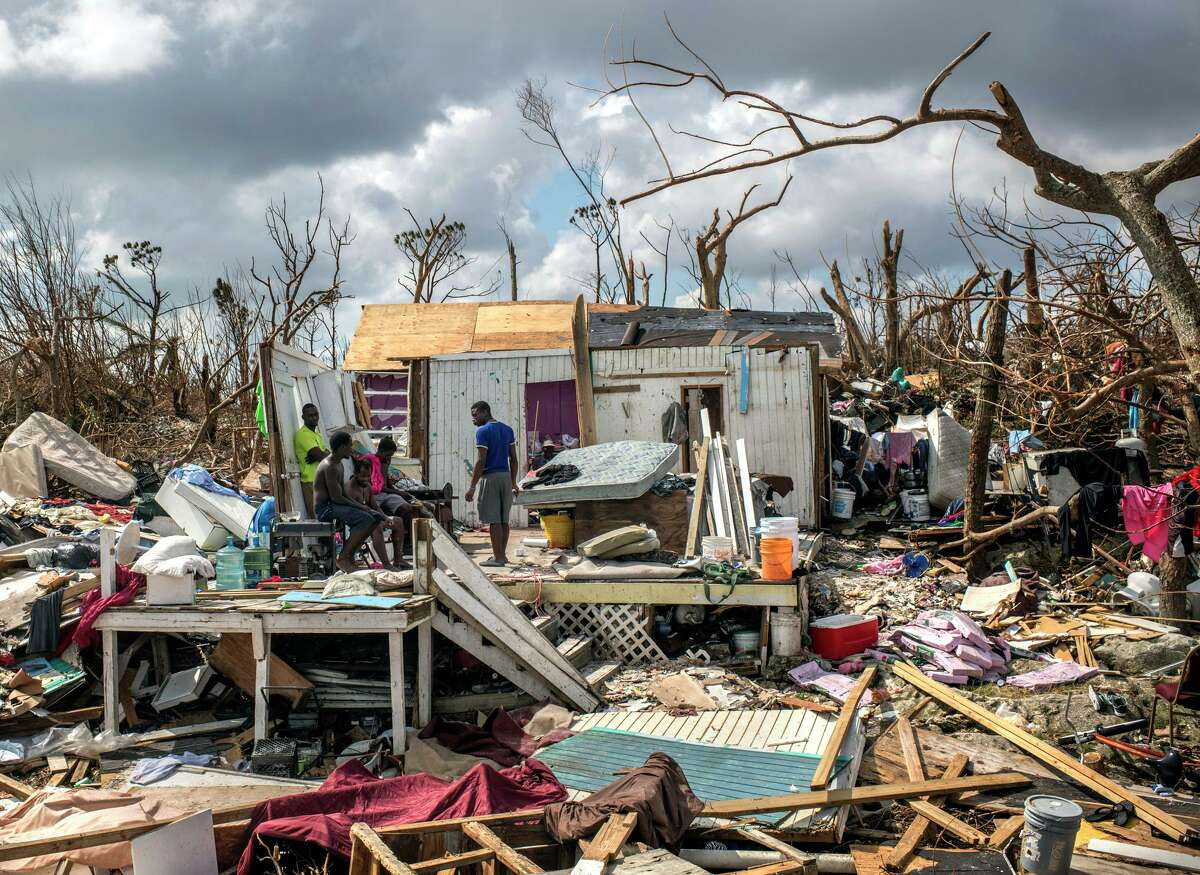 Survivors of Hurricane Dorian survey the wreckage of their home in Marsh Harbour, the Bahamas, on Friday, Sept. 6, 2019. Storms continue to grow more destructive due to climate change. (Daniele Volpe/The New York Times)