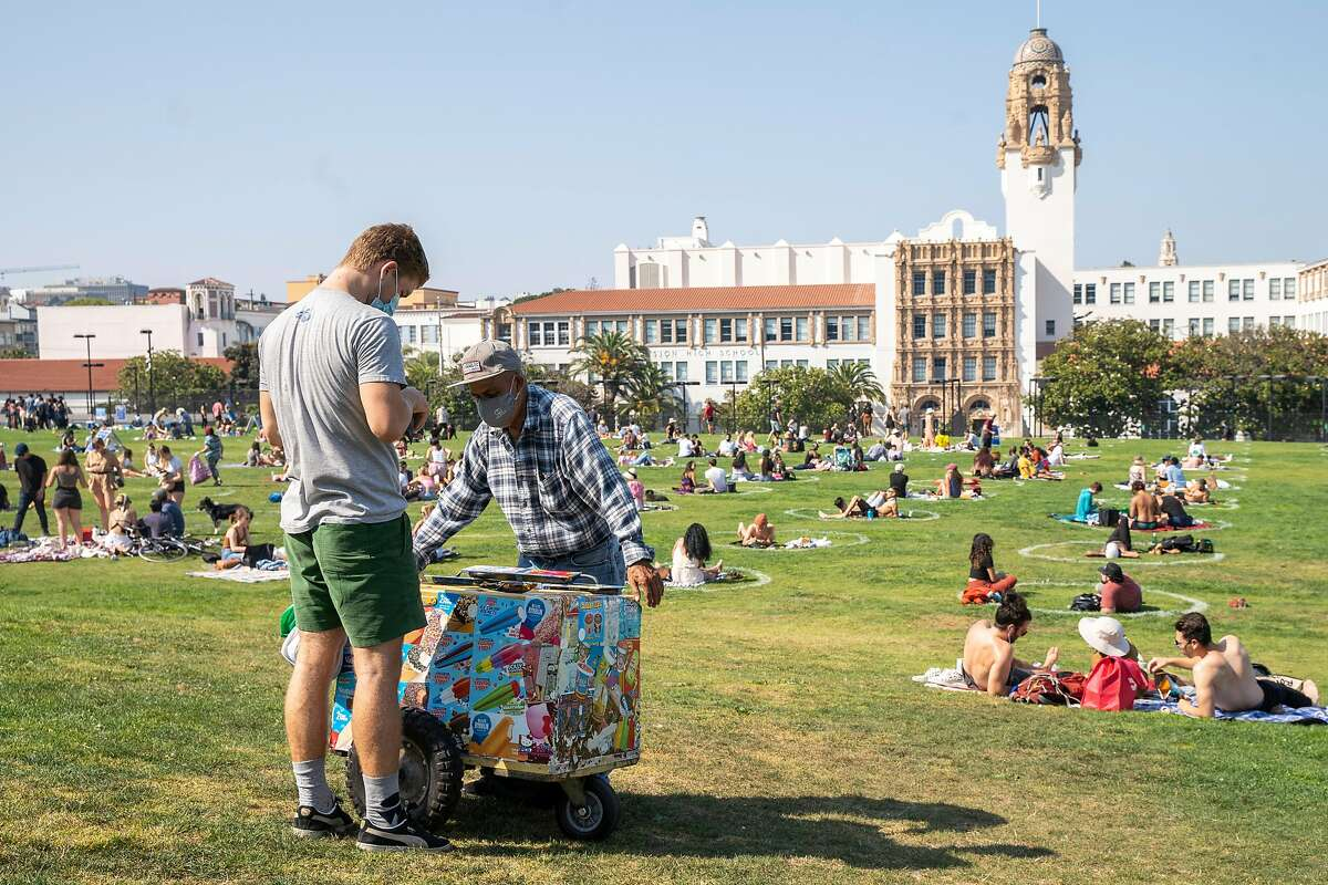 An ice cream vendor as people gather in the physical distancing circles during the Labor Day weekend at Dolores Park, Saturday, Sept. 5, 2020, in San Francisco, Calif.